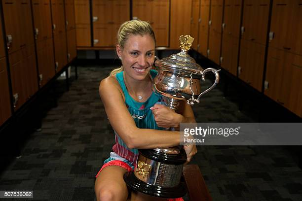 In this handout photo provided by Tennis Australia, Angelique Kerber of Germany poses with the Daphne Akhurst Trophy in the players change rooms...