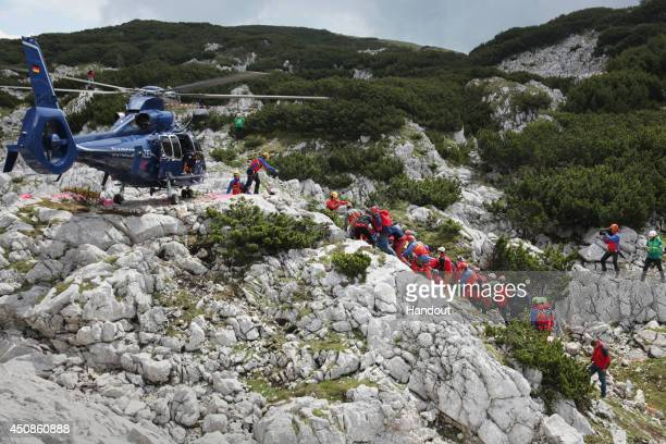In this handout photo provided by the Bavarian Mountain Patrol rescue workers carry injured spelunker Johann Westhauser to a waiting helicopter after...