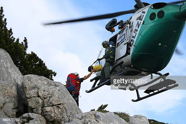 In this handout photo provided by the Bavarian Red Cross rescue workers unload supplises from a helicopter near the entrance to the Riesending...