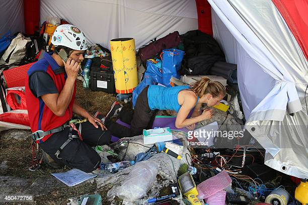 In this handout photo provided by the Bavarian Red Cross rescue workers gather at a tent near the entrance to the Riesending underground cave where...