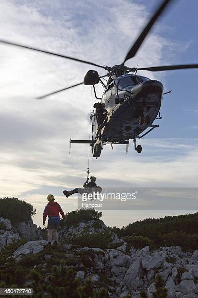 In this handout photo provided by the Bavarian Red Cross rescue workers arrive by helicopter near the entrance to the Riesending underground cave...