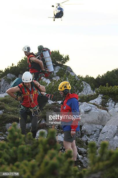 In this handout photo provided by the Bavarian Red Cross rescue workers gather near the entrance to the Riesending underground cave where an explorer...