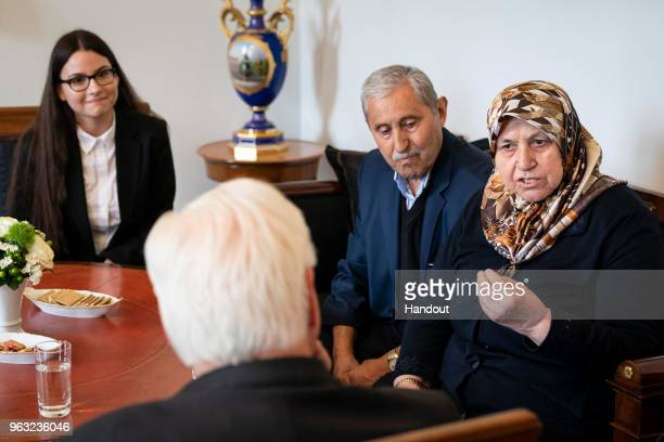 In this handout photo provided by the Federal President FrankWalter Steinmeier talks to Mevlude Genc who lost two daughters two granddaughters and a...
