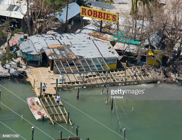 In this handout photo provided by the Florida Keys News Bureau workers make repairs to a dock at Robbie's Marina on September 19 2017 in Islamorada...