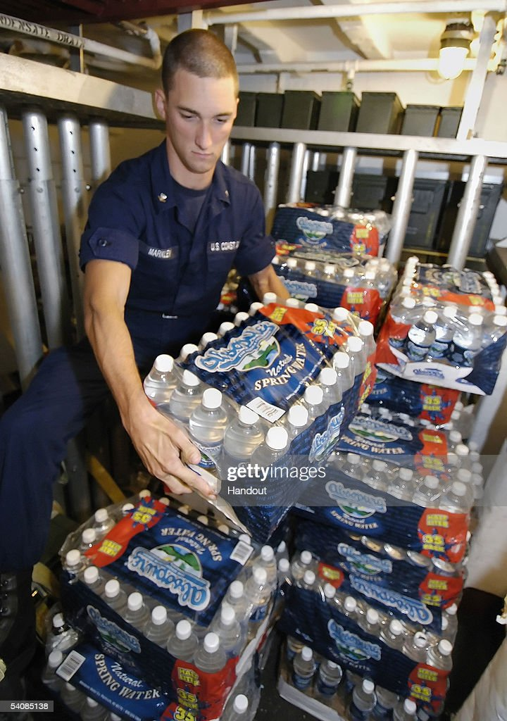 In this handout photo provided by the Florida Keys News Bureau, U.S. Coast Guard specialist Caleb Markley loads bottled water in the armory of the cutter Confidence on September 1, 2005 in Key West, Florida. Hours later the 210-foot-medium-endurance cutter departed for the Mississippi delta to serve as a command and control center for Coast Guard helicopters involved in post-Hurricane Katrina rescue operations. Onboard the vessel are other relief supplies for storm victims including nonperishable food and clothing donated by the Key West residents and tourism-related businesses.