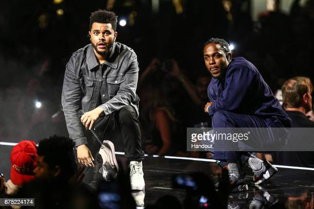 "In this handout photo provided by The Forum, Kendrick Lamar joins The Weeknd on stage during the ""Legends of The Fall Tour"" to perform ""Sidewalks"" on..."