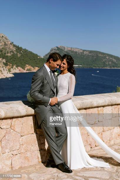 In this handout photo provided by the Fundacion Rafa Nadal Rafa Nadal poses with wife Xisca Perello for the official wedding portraits after they...