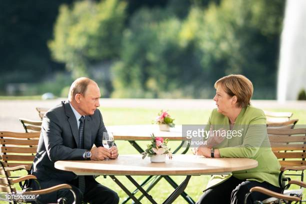 In this handout photo provided by the German Government Press Office German Chancellor Angela Merkel and Russian President Vladimir Putin meet at...