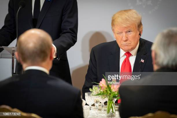 In this handout photo provided by the German Government Press Office US President Donald Trump sits opposite Russian President Vladimir Putin during...