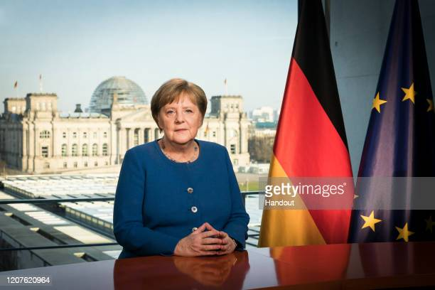 In this handout photo provided by the German Government Press Office , German Chancellor Angela Merkel addresses the nation via a video statement...