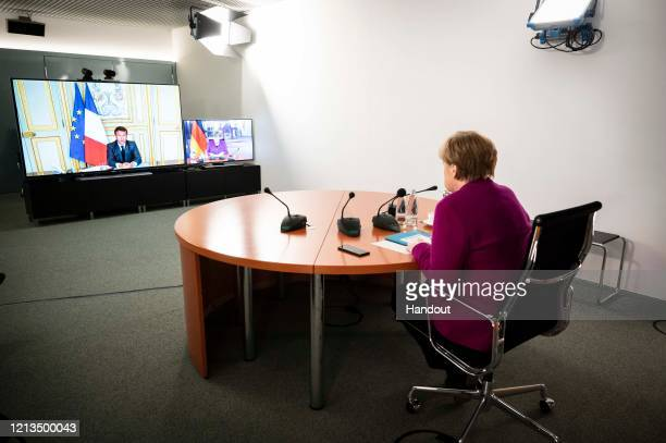 In this handout photo provided by the German Government Press Office German Chancellor Angela Merkel is seen during a video conference with French...