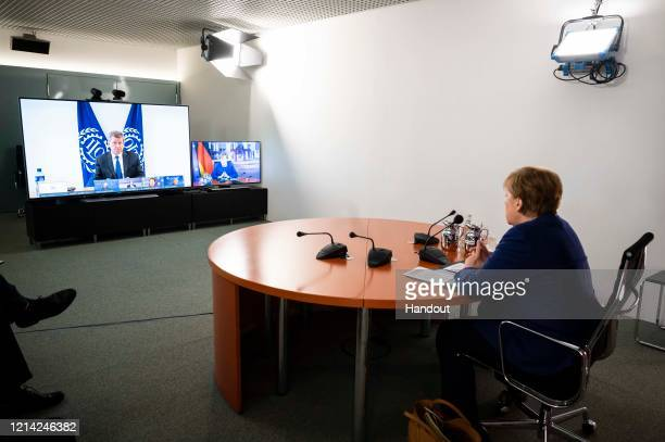In this handout photo provided by the German Government Press Office German Chancellor Angela Merkel looks on as Guy Ryder Director General of the...