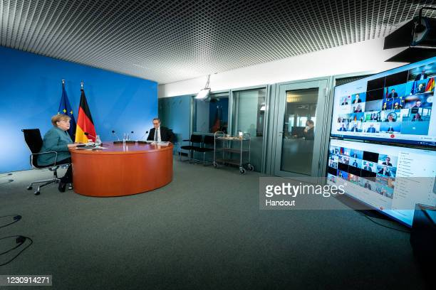 In this handout photo provided by the German Government Press Office , German Chancellor Angela Merkel and Berlin Mayor Michael Mueller lead a video...