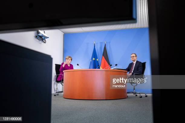 In this handout photo provided by the German Government Press Office , German Chancellor Angela Merkel and Berlin Mayor Michael Mueller sit before a...
