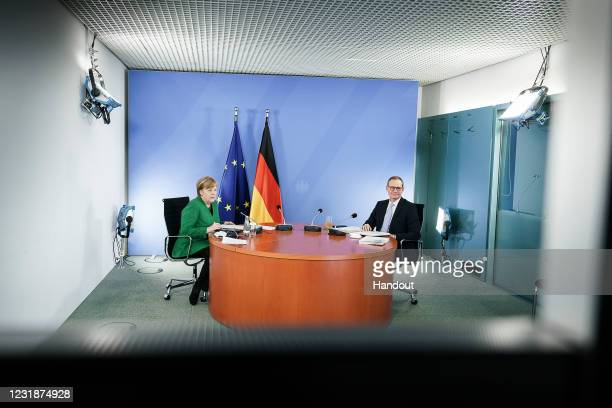 In this handout photo provided by the German Government Press Office , German Chancellor Angela Merkel and Berlin Mayor Michael Mueller attend a...