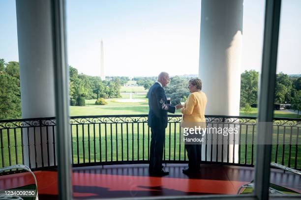 In this handout photo provided by the German Government Press Office , German Chancellor Angela Merkel and U.S. President Joe Biden stand in the...