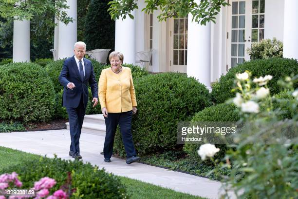 In this handout photo provided by the German Government Press Office , German Chancellor Angela Merkel and U.S. President Joe Biden walk to the joint...