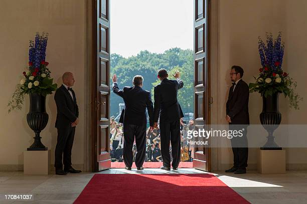 In this handout photo provided by the German Government Press Office , U.S. President Barack Obama and German President Joachim Gauck wave to the...
