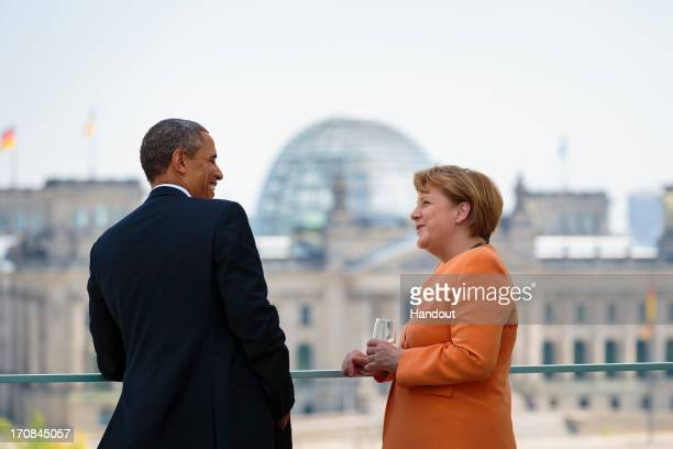 In this handout photo provided by the German Government Press Office US President Barack Obama and German Chancellor Angela Merkel chat prior to a...