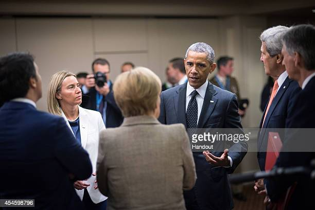 In this handout photo provided by the German Government Press Office German Chancellor Angela Merkel the EU's foreign policy chiefdesignate the...