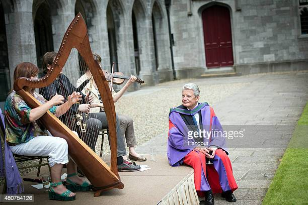 In this handout photo provided by the German Government Press Office German President Joachim Gauck listens to violine harp and Uilleann Pipes played...