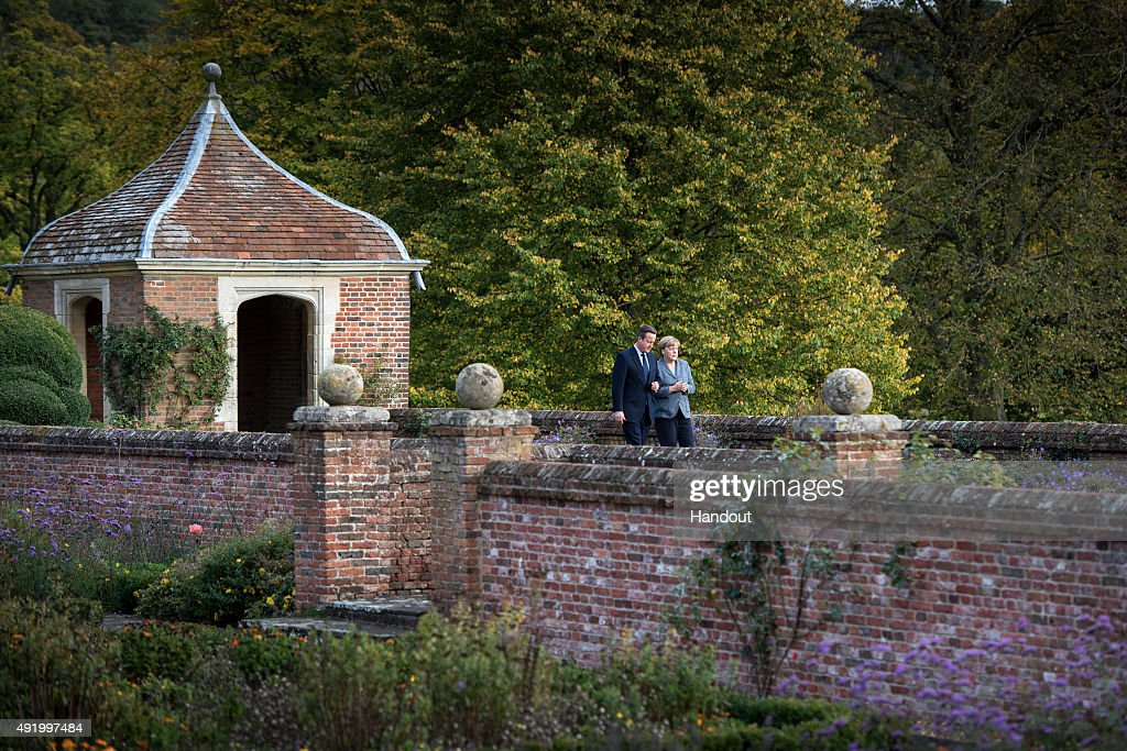 In this handout photo provided by the German Government Press Office (BPA), German Chancellor Angela Merkel and British Prime Minister David Cameron talk at the beginning of their meeting at Chequers, the Prime Minister's country residence on October 9, 2015 near Aylesbury, Buckinghamshire, United Kingdom. The meeting between the two leaders is expected to focus on Britain's EU renegotiation aims.