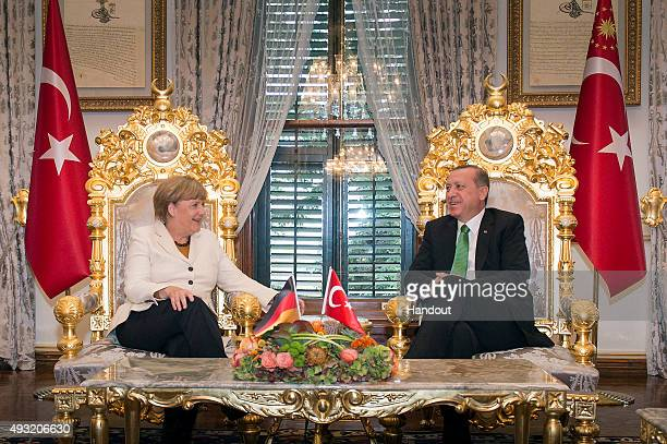 In this handout photo provided by the German Government Press Office German Chancellor Angela Merkel and Turkish President Recep Tayyip Erdogan talk...