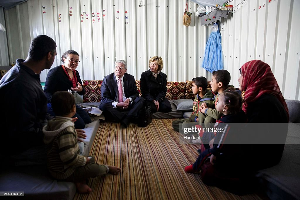 In this handout photo provided by the German Government Press Office (BPA) German President Joachim Gauck and his partner, Daniela Schadt speak with a Syrian family at their accomodation on March 16, 2015 in in Azraq, Jordan.