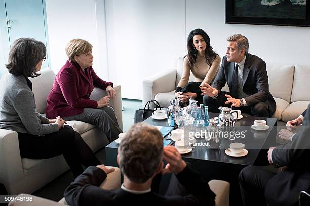 In this handout photo provided by the German Government Press Office Chancellor Angela Merkel meets with George Clooney and Amal Clooney at the...