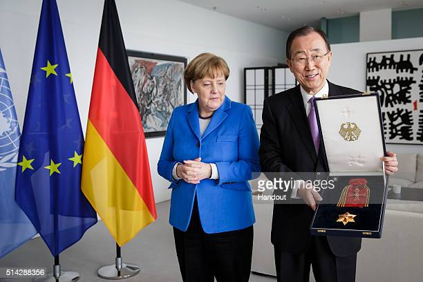 In this handout photo provided by the German Government Press Office , Chancellor Angela Merkel hands over to UN secretary general Ban Ki-moon The...