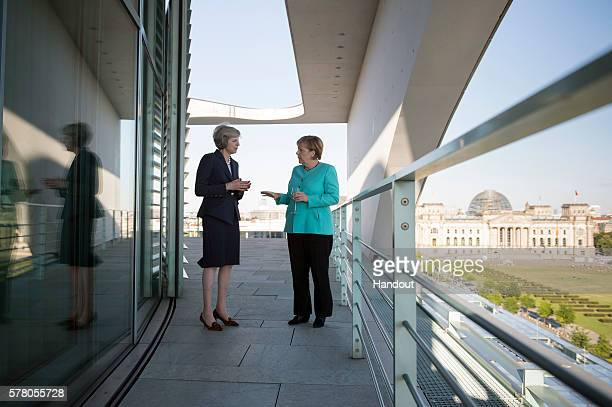 In this handout photo provided by the German Government Press Office German Chancellor Angela Merkel and British Prime Minister Theresa May talk...
