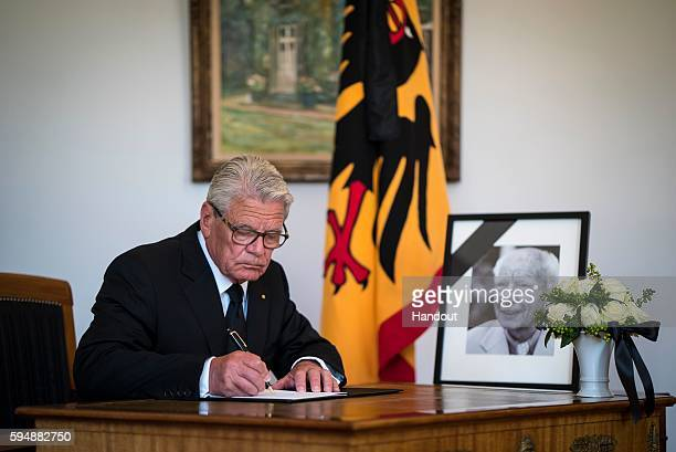 In this handout photo provided by the German Government Press Office German President Joachim Gauck signs a book of condolence for former President...