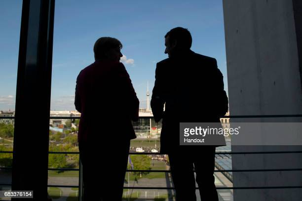 In this handout photo provided by the German Government Press Office German Chancellor Angela Merkel chats with newlyelected French President...