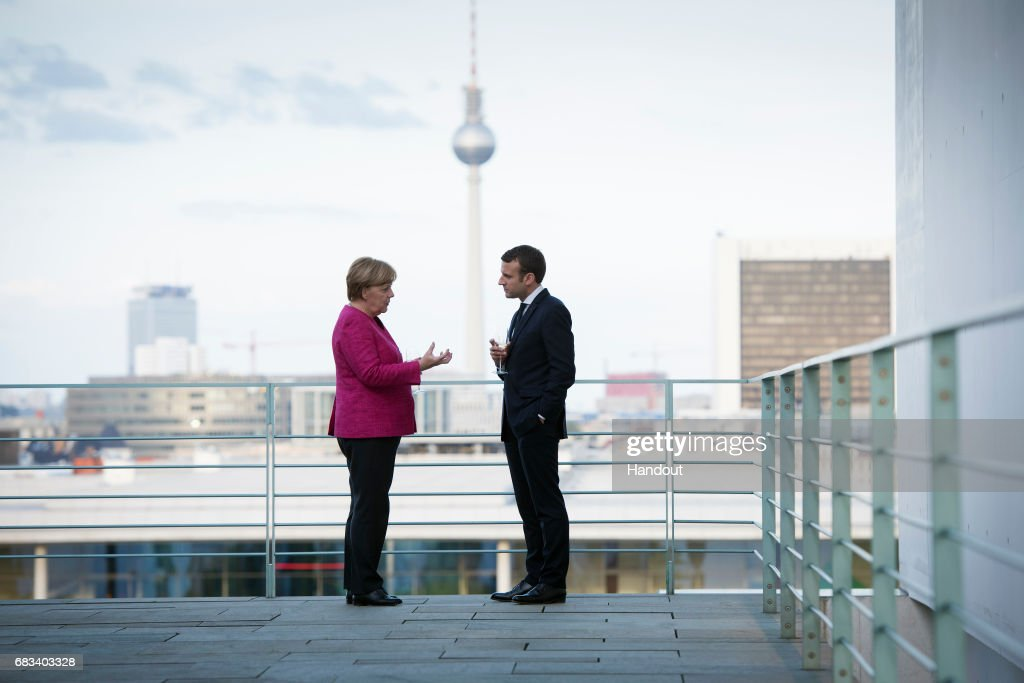 In this handout photo provided by the German Government Press Office (BPA), German Chancellor Angela Merkel talks with newly-elected French President Emmanuel Macron on the terrace, with a view of the television tower in the background during his visit to the chancellor's office on May 15, 2017 in Berlin, Germany. Macron is visiting Berlin only a day after being sworn in as president in Paris. While Macron and Merkel have both demonstrated an unwavering commitment to the European Union and Merkel strongly applauded Macron's election, they are likely to differ over Macron's desire for E.U.-issued bonds, a measure Merkel has strongly opposed in the past.