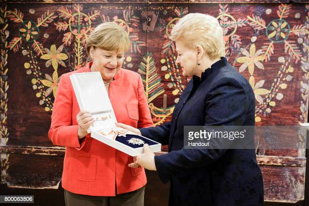 In this handout photo provided by the German Government Press Office Lithuanian President Dalia Grybauskaite gives Federal Chancellor Angela Merkel...