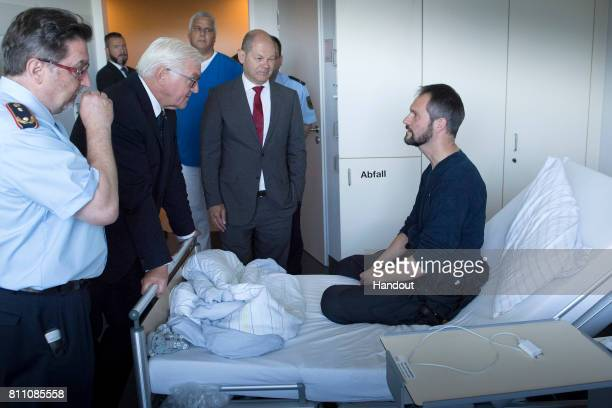 In this handout photo provided by the German Government Press Office German President FrankWalter Steinmeier visits a police officer who was a victim...