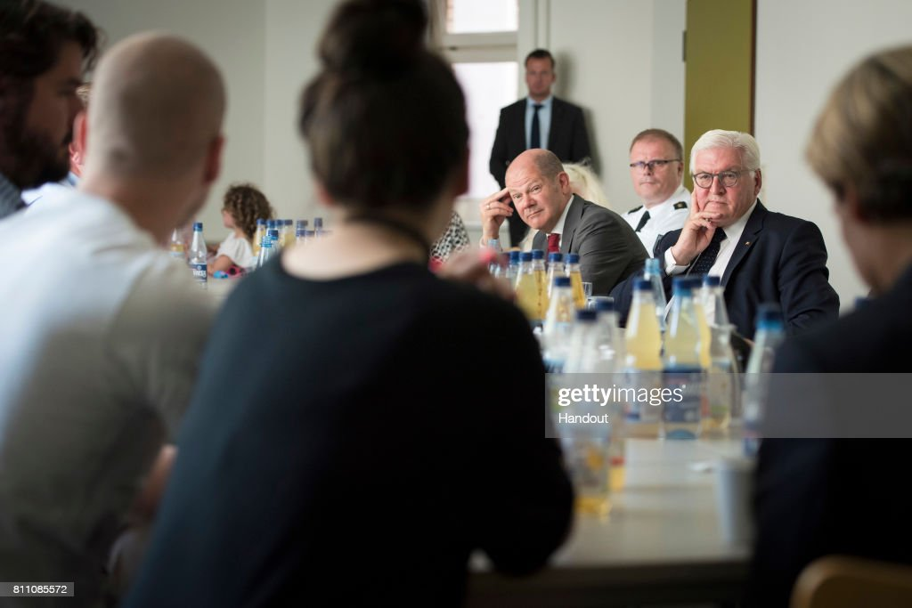 In this handout photo provided by the German Government Press Office (BPA), German President Frank-Walter Steinmeier and Mayor of Hamburg, Olaf Scholz, talk to businessmen from the Schanzenviertel, whose businesses was plundered due to the violence that broke out at the G20 summit on July 9, 2017 in Hamburg, Germany.