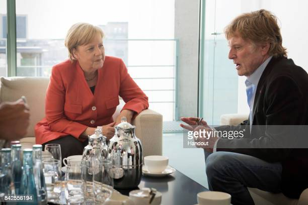 In this handout photo provided by the German Government Press Office German Chancellor Angela Merkel and US actor Robert Redford at the beginning of...