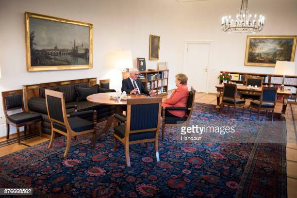 In this handout photo provided by the German Government Press Office Chancellor Angela Merkel and Federal President FrankWalter Steinmeier hold a...