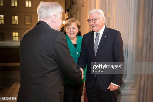 In this handout photo provided by the German Government Press Office German President FrankWalter Steinmeier greets Horst Seehofer Governor of...
