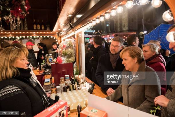 In this handout photo provided by the German Government Press Office Chancellor Angela Merkel talks with the operators of a booth that was one of the...