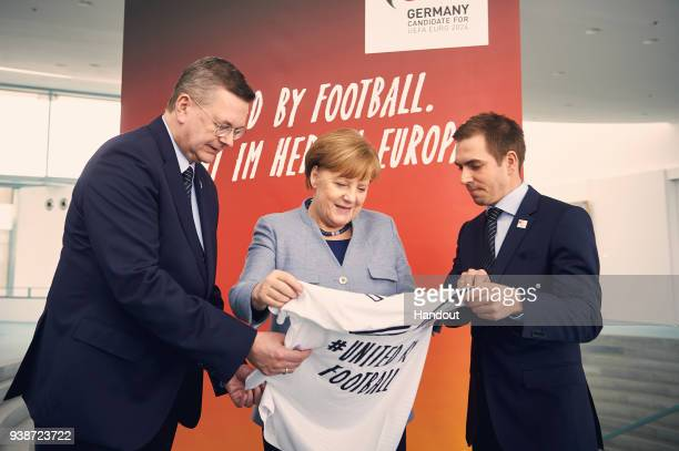 In this handout photo provided by the German Government Press Office German Chancellor Angela Merkel receives a jersey by DFB President Reinhard...