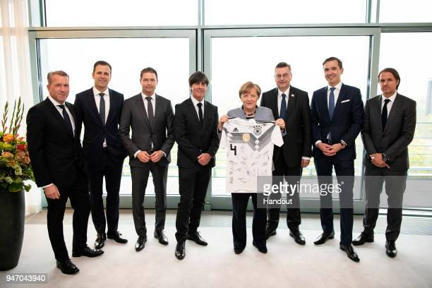 In this handout photo provided by the German Government Press Office German Chancellor Angela Merkel receives a World Cup jersey signed by players...