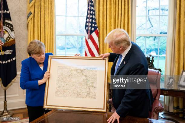 In this handout photo provided by the German Government Press Office Chancellor Angela Merkel hands a historic map of the Rheinpfalz from 1705 the...