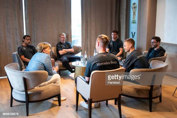 In this handout photo provided by the German Government Press Office German Chancellor Angela Merkel talks to Leroy Sane Julian Brandt MarcAndre ter...