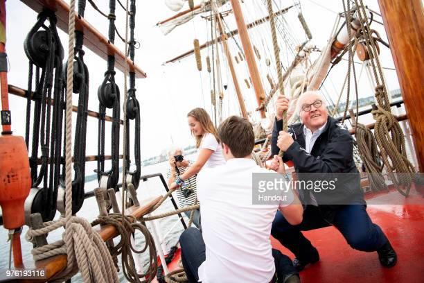 In this handout photo provided by the German Government Press Office German President FrankWalter Steinmeier helps hoist a sail on the ship 'Thor...