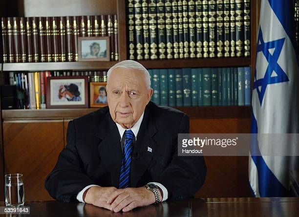 In this handout photo provided by the Government Press Office, Israeli Prime Minister Ariel Sharon delivers a televised address from his office...