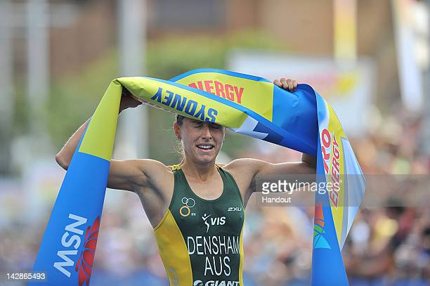 In this handout photo provided by the International Triathlon Union Australia's Erin Densham raises the finish tape after winning the opening round...