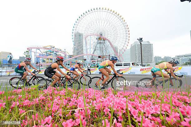 In this handout photo provided by the International Triathlon Union competitors ride past a roundabout during the bike leg of the ITU World Triathlon...