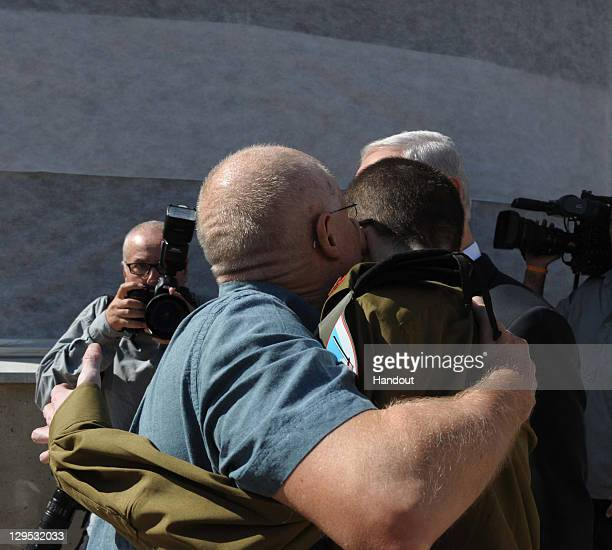 In this handout photo provided by the Israeli Defence Force freed Israeli soldier Gilad Shalit hugs his father Noam Shalit in front of Israeli Prime...